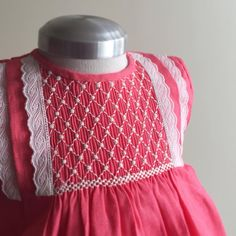 Freda - Darling smocked dress incorporating swiss edging on hot pink.