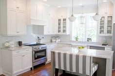gorgeous white kitchen. Striped bench, white marble counters, and dark floors