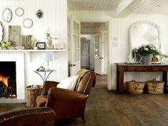 wohnzimmer coutry style brauner ledersessel holzkamin weiß gestrichene holz wandverkleidung
