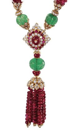 RUBY & EMERALD BEAD & DIAMOND TASSEL-NECKLACE, VAN CLEEF & ARPELS, NEW YORK, c 1970.  The necklace composed of segments of ruby beads held within gold & diamond caps, spaced by fluted emerald beads & diamond rondelles, the center decorated with a lozenge-shaped segment centering a ruby bead framed by round diamonds & rubies, supporting a ruby bead tassel surmounted by emerald and ruby beads,  mounted in 18  karat gold, tassel detaches to be worn as a brooch, signed V.C.A.