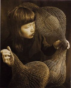 Ruth Asawa holding a form-within-form sculpture. Photo by Imogen Cunningham, 1952.