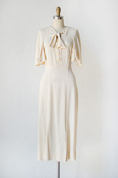 1930's dress made from an ivory silk rayon features a v-neckline with a sailor bow tie detail at the front center, large button closures down the front center, and 3/4 flutter sleeves. The dress tapers in at the waist and flows straight down at the hips.