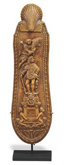 A LARGE LOUIS XV BOXWOOD SNUFF RASP  DATED 1727  Carved with a portrait of the King on a plinth adorned with the Royal Arms with slaves at the base and an angel above, the reverse with a metal grater with a shell dated 1727 at the top and a Coat-of-Arms at the base  9¼ in. (23.5 cm.) long (2)