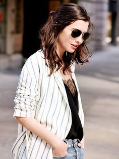 Statement earrings are worn with a striped blazer, lace-neck camisole and aviators.