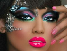 Gorgeous spectrum of eye shadow accented with clear gems and vibrant pink lips.