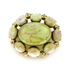A fabulous brooch featuring beautiful green dragons breath style stones. Each stone has trails of gold aventurine embedded into the glass with...