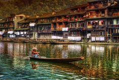 It was a cool and calm afternoon in the ancient and impossible town of Feng Huang. It's an old town, wreathed in many legends.  On the old river, you can occasionally see a boat passing here and there. The boatmen come in all shapes and sizes, but many wear the same hat and style. It is absolutely like a warp of time… - Feng Huang, China - Photo from #treyratcliff Trey Ratcliff at http://www.StuckInCustoms.com