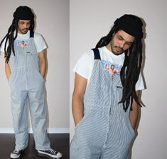 dreadlocks in dark brown, worn by a man with a black beanie hat, 90s aesthetic, a white t-shirt with colorful print, and pinstriped overalls