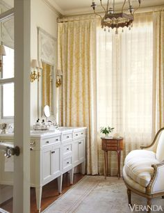 An airy, sun-soaked bathroom is reborn with a mix of fine French antiques and creamy yellow fabrics. Design by Jane Schwab.