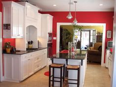 This classic red kitchen features bright white cabinets and a sleek black countertops. Neutral tile flooring and white crown molding balance the vibrant wall color.