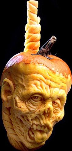 A grotesque creature (is it a goblin?) was carved into this pumpkin by Ray Villafane