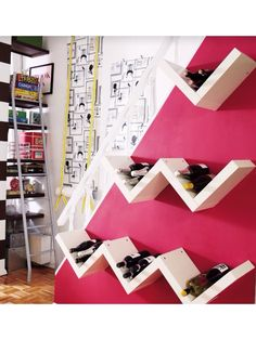 DIY wine storage: Arrange wood boards in a chevron design. Screw together and hang on the side of a staircase.