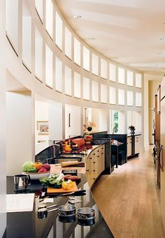 KITCHEN – A chefs own kitchen, such an interesting shape that opens to the next room..kind of like an open air kitchen! Architectural Digest.