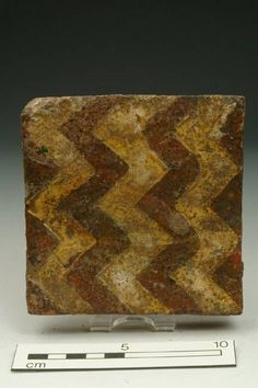 tile; floor tile  Accession number: 84.8/5 Production date: Early Medieval; mid-late 13th century Material: ceramic; earthenware Measurements: T 21 mm; L 116 mm; W 115 mm Museum Section: Medieval Summary: Floor tile, Westminster; horizontal zig-zag.