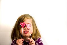Little girl holding up valentine's day lollipops over her eyes - 5 things you don't need to do in order to be a good parent on valentine's day