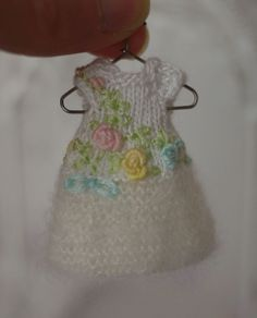 A hand knit and embroidered dress for Amelia Thimble dolls, bullion stitched roses, lazy daisy bow.