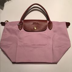 Longchamp Le Pliage Mini Tote Authentic Longchamp light baby pink fold-up mini tote. Brand new but very minor marks at the folding lines due to storage (see the last photo), barely noticeable. That's why it is listed for $80.  This bag is sold for $95 at department stores. Longchamp Bags Totes