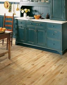 Light hardwood flooring and a pop of color with the deep teal cabinets!