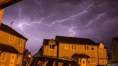 Lightning seen over houses at night.Wiltshire UK
