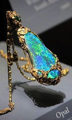 "The Tiffany Opal Necklace, designed by L.C. Tiffany circa 1929. This pendant features a 30"" 18kt gold chain, green demantoid garnets (Russia), and black opals (from Lightning Ridge, Australia). The black opals have a great blue-green play of color (a.k.a. opalescence)."