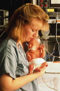 Nurse with infant in neonatal intensive care unit