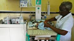 A nurse attaches the low-cost breathing machine (far left) to an infant at The Queen Elizabeth Central Hospital in Blantyre, Malawi. (NPR)