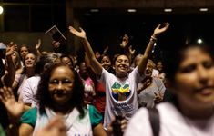 """A young woman raises her arms during a Mass April 12 to mark the start of the 100-day countdown to World Youth Day in Rio de Janeiro. World Youth Day 2013, an annual international Catholic event, runs from July 23 to 28 in Rio de Janeiro. The words on the woman's t-shirt has the name of Pope Francis as """"Francisco,"""" as he is known in the Spanish-speaking world. CNS photo/Ricardo Moraes, Reuters)"""