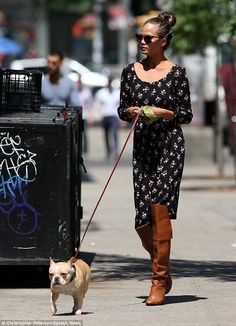 Doggy duty: Chrissy Teigen donned over-the-knee leather boots and a long patterned dress to take her dog Pippa for a walk http://dailym.ai/1r0OReB