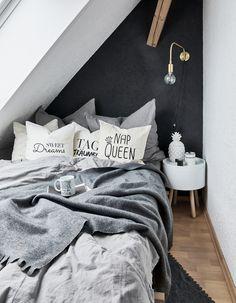 Nap Queen! Mit der dunklen Wand ist ein wohnliches Highlight im Schlafzimmer garantiert, wobei die weißen Kissen und die graue Bettwäsche Willow für den perfekten Kontrast sorgen. Süße Botschaften auf den Kissen sorgen bereits am Morgen für gute Laune! // Schlafzimmer Kissen Bettwäsche Decke Nachttisch Schwarz Wandfarbe Monochrom Bett Ideen #SchlafzimmerIdeen #Bettwäsche #Dekoration
