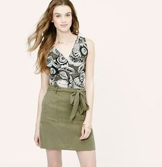 Adorned with retro-cool tropic florals, a twisted back design stylizes this summery favorite. V-neck. Sleeveless. Gathered elasticized detail at back.