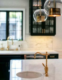 dark cabinetry, calcatta backsplash tile, aged brass fixtures, black window, white counters/walls
