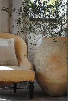 terra cotta pot next to a comfy chair, what a lovely nook :)