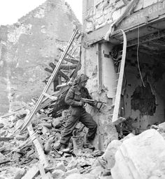 A Canadian soldier, armed with a German weapon, searches through the rubble in Caen