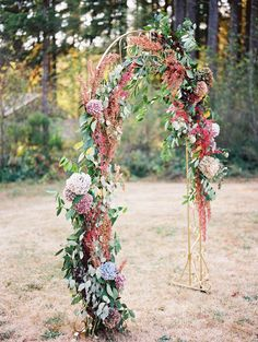 The florals and foliage really compliment this gold wedding arch beautifully.