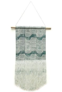 """A 100% natural cotton canvas wall hanging with a block printed wave design in blue ink.Dimensions: Measures 10.5"""" x 22.5"""".Details: Wooden rod, fringe at the edge, with the print extending on to the fringe.Julia Canright is a bag maker, block printer and a San Francisco native. She creates bold an..."""