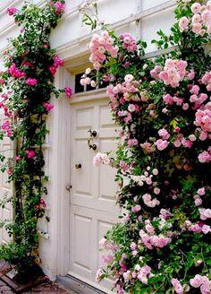 Flores rosas y fucsias adornan esta entrada blanca