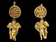 A PAIR OF GREEK GOLD EARRINGS  HELLENISTIC PERIOD, CIRCA LATE 4TH-3RD CENTURY B.C.  Each with a pan-shaped disk, the upturned edge decorated with beaded wire, the disk centered by a rosette, the petals rimmed with beaded wire, beaded wire double-spirals behind the petals, each with a hooked wire on the reverse formed into a loop which supports a solid-cast figure of Eros, the pair antithetically posed, with one leg advanced, their separately-made wings outstretched