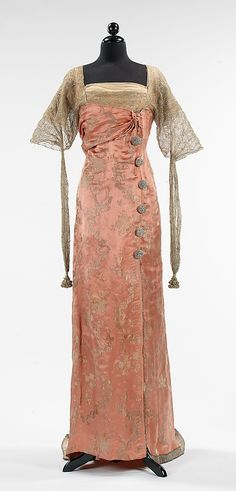 Pandora's: Early 20th Century Fashion      Evening dress (1914) by Callot Soeurs made of silk, metal and rhinestones, the fashion aesthetic of the time, in which multiple layers and textures of fabric were intended to give the appearance of an unstructured and spontaneous design. The use of the selvedge edge at the front of the dress, for example, was an intentional technique used by couturiers of the period to express the idea that fabric was wrapped and draped with minimal tailoring.""