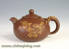 Red yixing teapot with chrysanthemum stretching from handle across the body flecked with gold highlights
