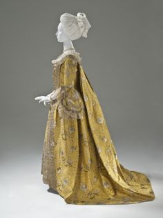 Side view, robe à la Francaise, England, c. 1760. Yellow silk plain weave with weft-float patterning and silk with metallic-thread supplementary-weft patterning, and metallic lace.