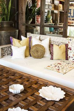 Hand carved day bed, hand embroidered pillows, carved coffee table crafted from antique ceiling.