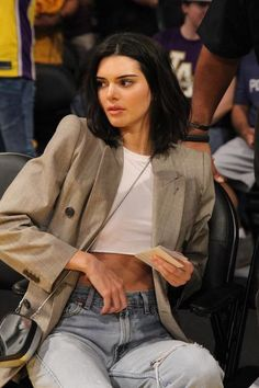 Kendall Jenner wearing a plaid double breasted blazer, white crop top, loose ripped jeans, crossbody bag, and white mules