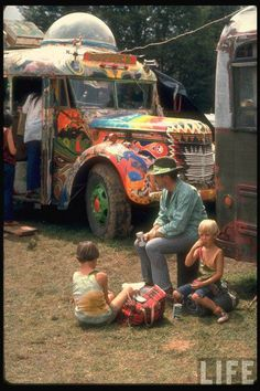 Man Seated with Two Young Boys in Front of a Wildly Painted School Bus, Woodstock Music Art Fest  John Dominis