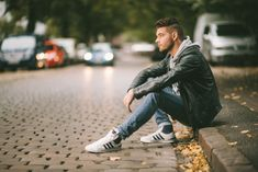 Pose: sitting on curb, arms in knees, back slouched Angle: Side on Background: cars, footpath and road