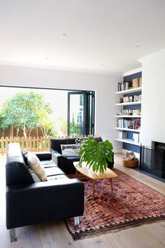 Easy breezy open living room with leather sofas and tribal rug. Lei & Dijon's Stylish, Quirky Home in Cape Town