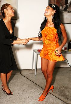 Beyoncé Knowles in a black wrap dress and black heels // Solange Knowles in a bright orange dress with matching orange heels