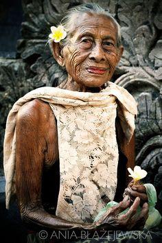 Indonesia, Bali. Portrait of a beautiful elderly Balinese lady selling flowers in Pura Beji temple in Sangsit.