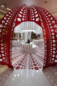 The exhibited materials, bags and shoes are all a part of the dot-inspired concept and are well emphasized with the help of a visually powerful lighting scheme. Perforated giant lamps hang over the display tables, which are in tune with the red floor and walls.