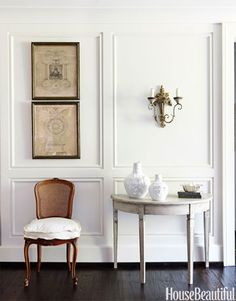 Walls painted China White by Benjamin Moore set off a Swedish demilune table and French pen-and-inks.