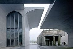 Shanghai's Long Museum, completed in 2014 by the city's Atelier Deshaus, was built around a 1950s bridge and a parking garage. Its cantilevered form features giant cast-in-place concrete curves juxtaposed with transparent metal walls.